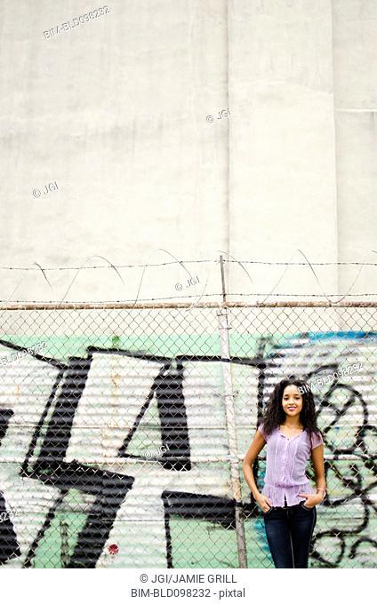 Middle eastern woman standing near graffiti