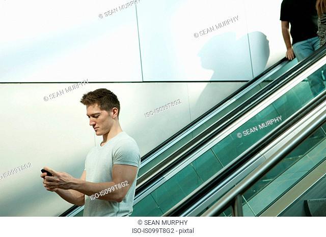 Young man on escalator using smartphone