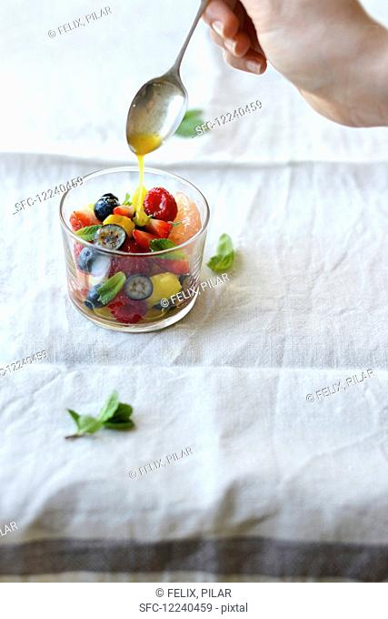 A fruit salad being drizzled in a basil and mint citrus syrup