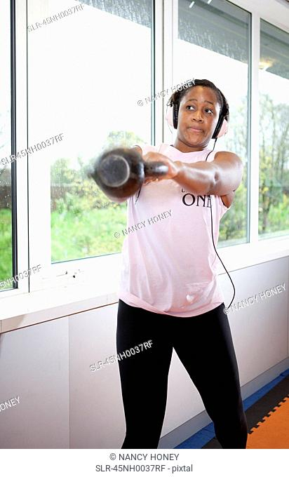 Teenage girl lifting weights in gym