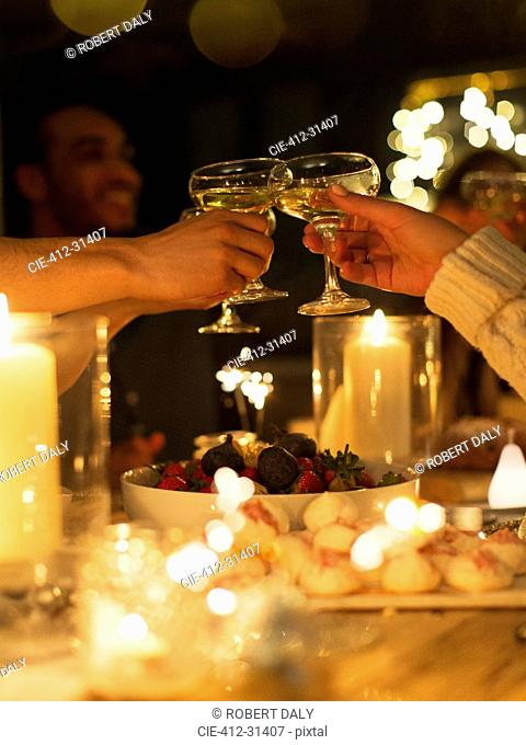 Friends toasting champagne glasses over table at candlelight Christmas dinner