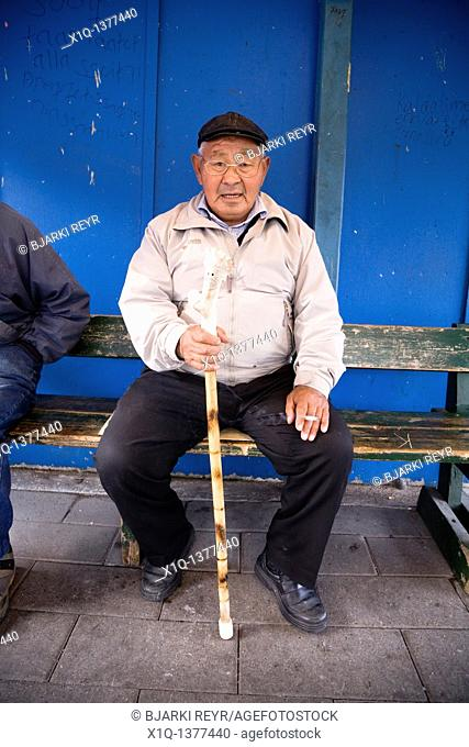 At the fish market, Narsaq, South Greenland  The handle on the walking stick is made from reindeer horn