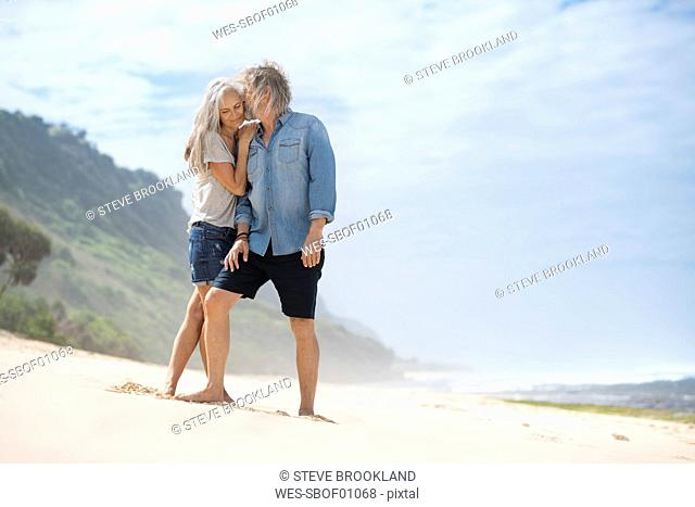 Affectionate senior couple standing on the beach