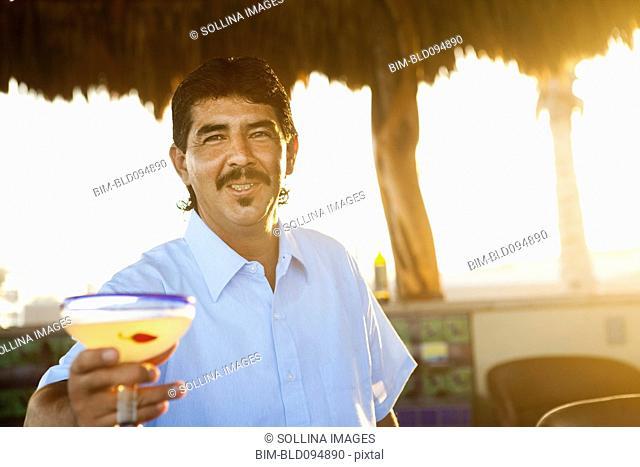 Hispanic bartender serving cocktail
