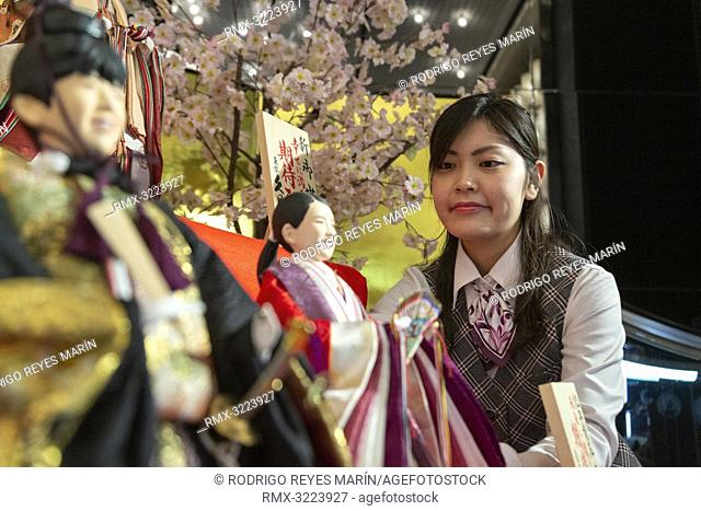An employee looks at Japanese 'hina' dolls modeled after shogi player Sota Fujiii (L) and figure skater Rika Kihira (R) at Kyugetsu Company's showroom