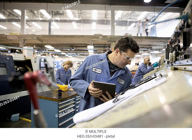 Worker with digital tablet examining machinery in factory