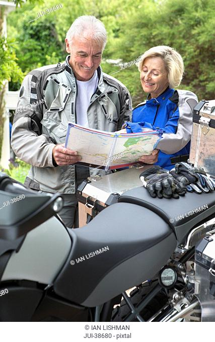 Senior couple looking at map next to motorcycle