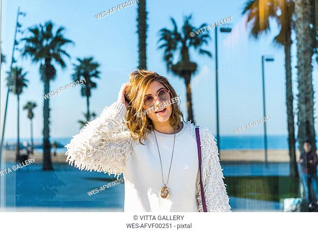 Portrait of young woman wearing sunglasses with palms in background