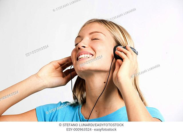 Teenage girl listening to the music, isolated on white