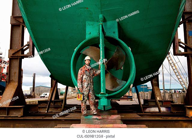 Portrait of male ship painter in front of green ship propeller