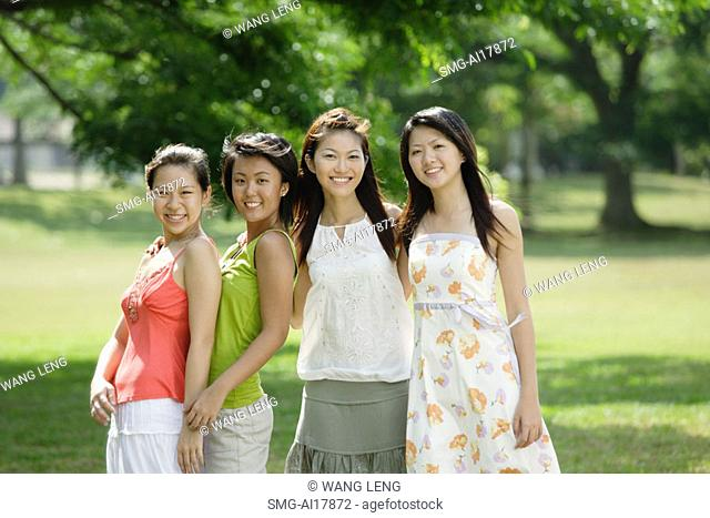 Young women standing side by side, looking at camera