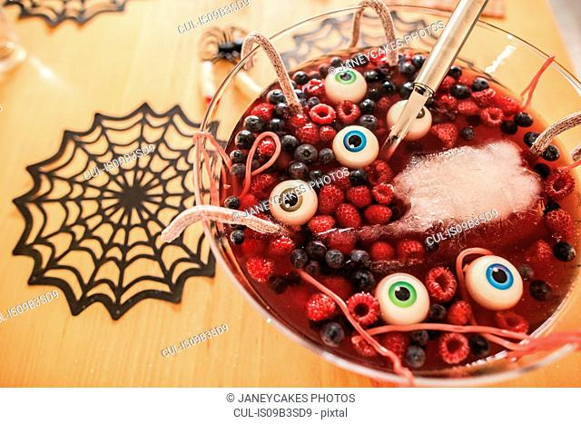 Halloween dessert with berries and floating eyeballs, close-up