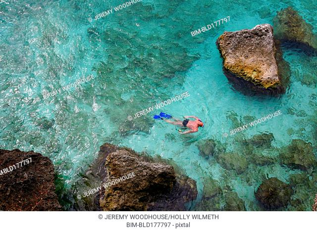 Overhead view of man snorkeling in tropical coral reef