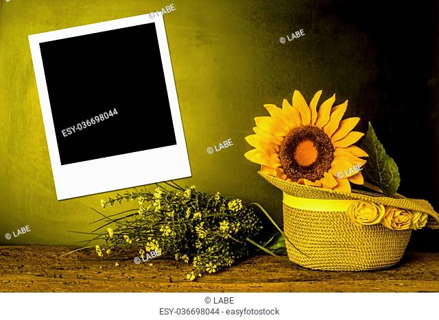 Empty instant photo frame, summer hat and sunflower background