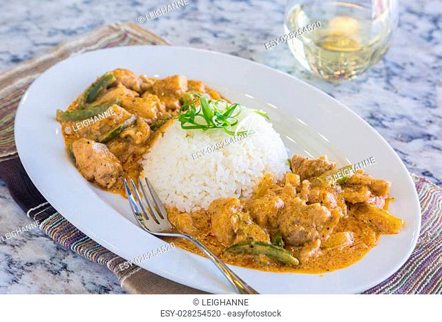 Chicken thighs and green bell peppers in panang curry sauce, served with rice