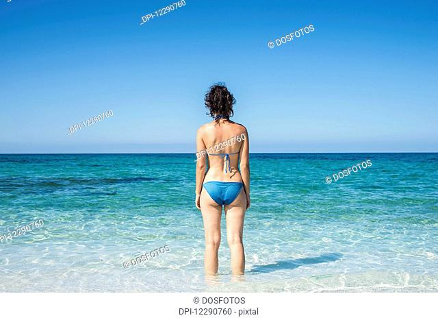 Young woman in a blue bikini at Mari Ermi beach, also known as the beach of the grains of rice; Oristano, Sardinia, Italy