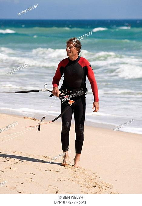 tarifa, cadiz, andalusia, spain, a man on punta paloma beach wearing a wetsuit and carrying kitesurfing equipment