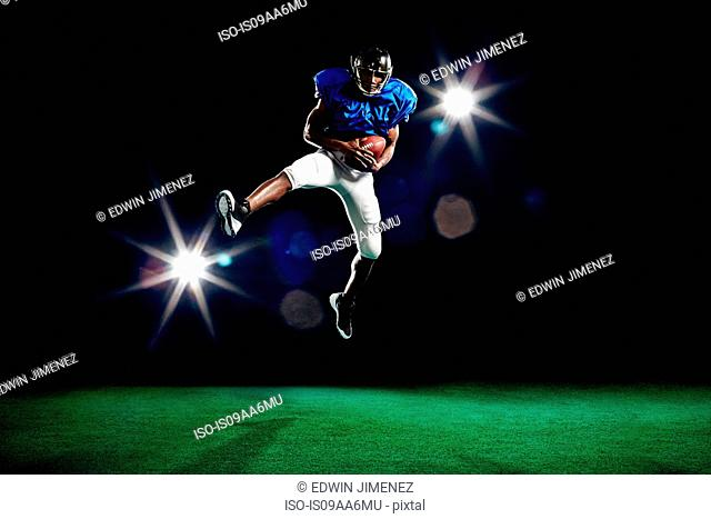 American football player jumping with ball