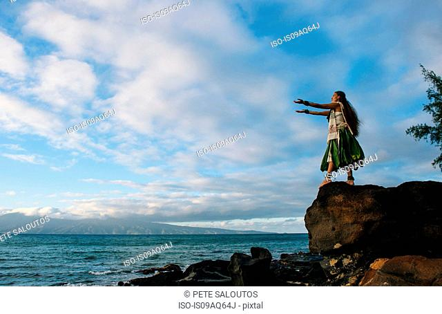 Woman hula dancing on top of coastal rocks wearing traditional costume, Maui, Hawaii, USA