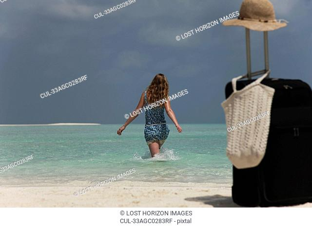 Woman abandoning luggage on beach