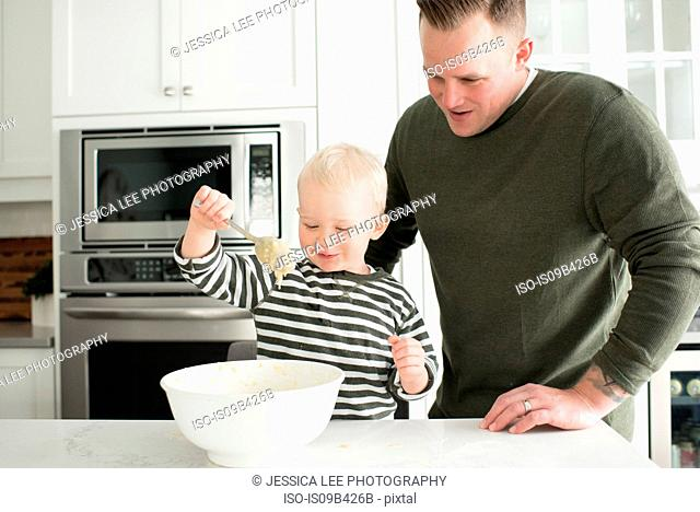 Father and son baking together, son mixing mixture