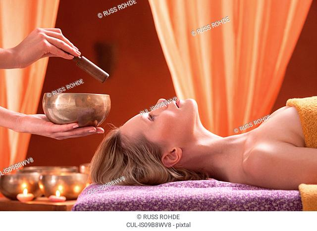 Woman in spa environment, having relaxation treatment, therapist holding Tibetan bowl