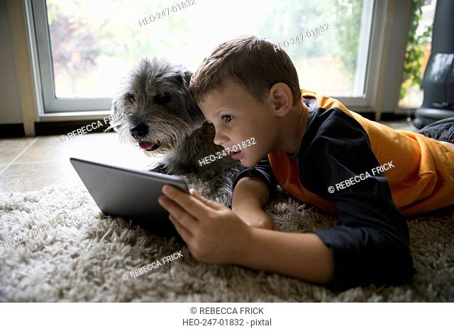 Boy and dog using digital tablet on floor