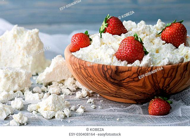 A wooden bowl with cottage cheese and fresh strawberries on a bluish background