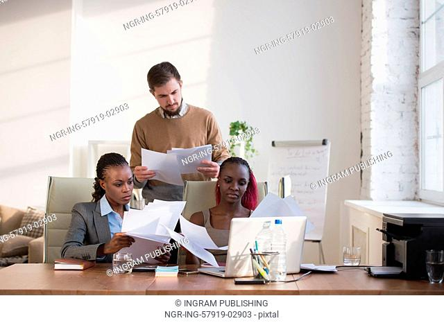 Image of group of three young business people of different ethnicity working together