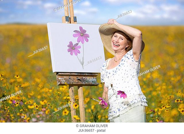 Portrait of smiling woman painting in sunny wildflower meadow