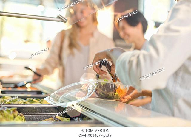 Young woman serving salad at salad bar in grocery store market