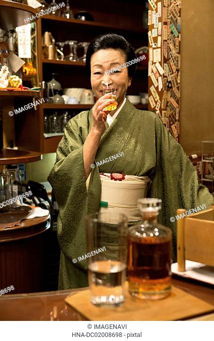 Senior Japanese woman in kimono drinking sake
