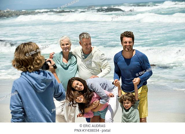 Boy filming his family with a home video camera on the beach