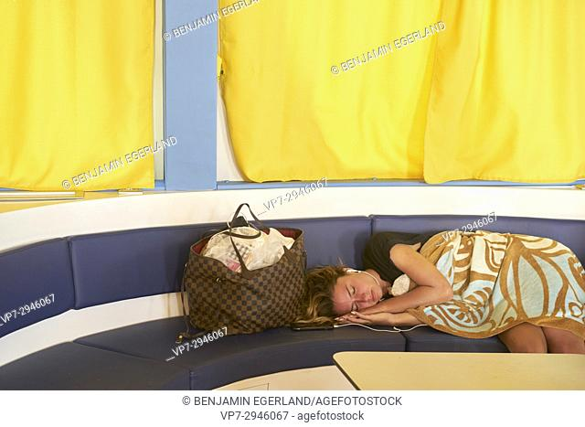 exhausted girl sleeping at the bench in a ferry. Dutch ethnicity. On the way to holiday destination Chrissi Island, Crete, Greece