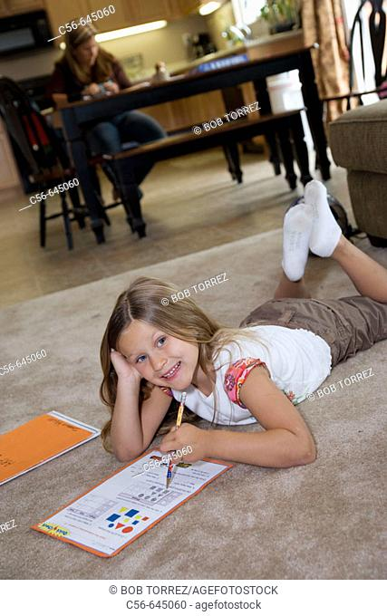 smiling young girl does her homework on floor, mother in background