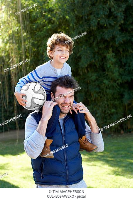 Father carrying smiling son holding football on shoulders
