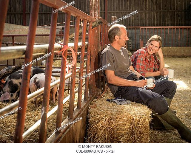 Farming couple taking a break in barn