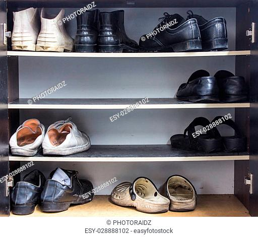 Shoes, gym shoes, boots and other footwear stand on a rack