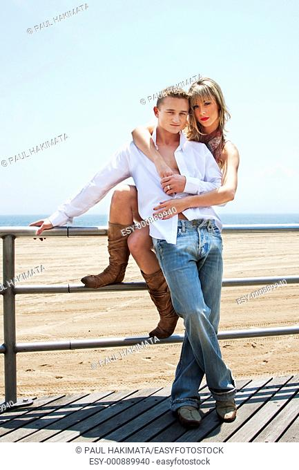 Young romantic sexy couple, man and woman, next to railing on the boardwalk at the beach standing together with her arms him