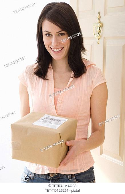 Portrait of woman holding package in doorway