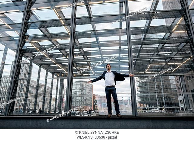 Germany, Berlin, businessman with arms outstretched standing in front of glass pane