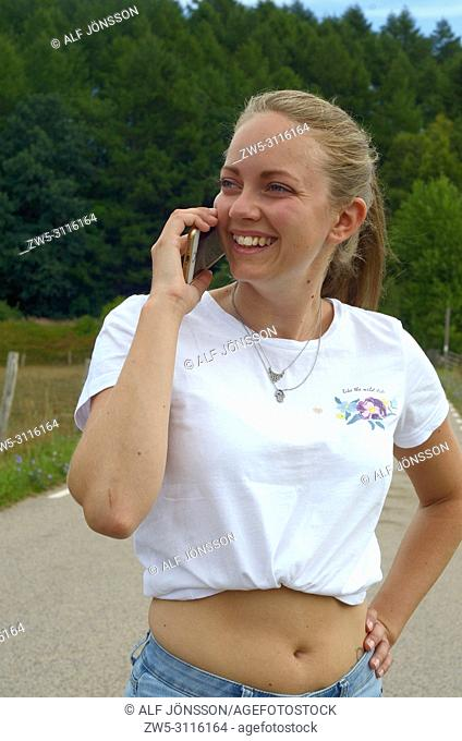 Young woman, 25 years old, talks in a mobil phone on a country road in Scania, Sweden, Europe