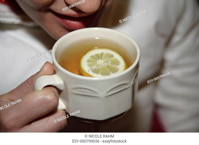 Young woman holding cup of tea with slice of lemon in it, close up