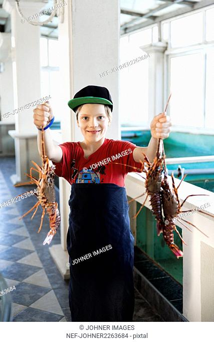 Boy holding lobsters