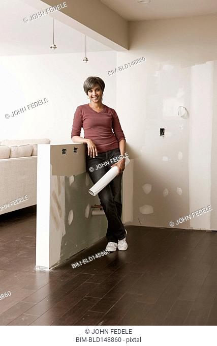 Mixed race woman standing in unfinished room with blueprints