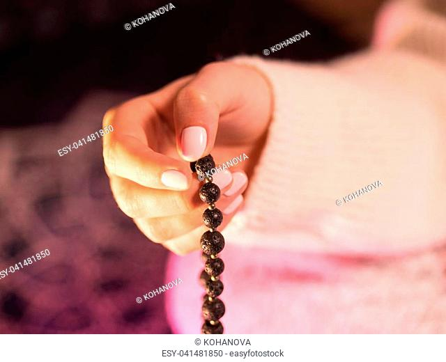 Woman, lit hand close up, counts Malas, strands of gemstones beads used for keeping count during mantra meditations