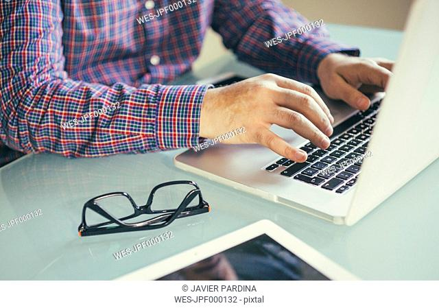 Man using laptop at desk, partial view