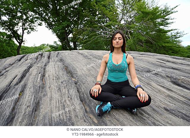 Attractive young mixed race woman practicing yoga in Central Park, New York City