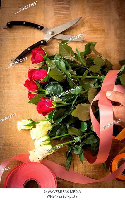Male florist tying poly ribbon on bouquet of flower