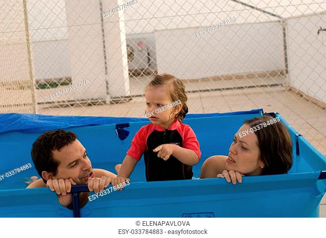 The happy family play in swiming pool